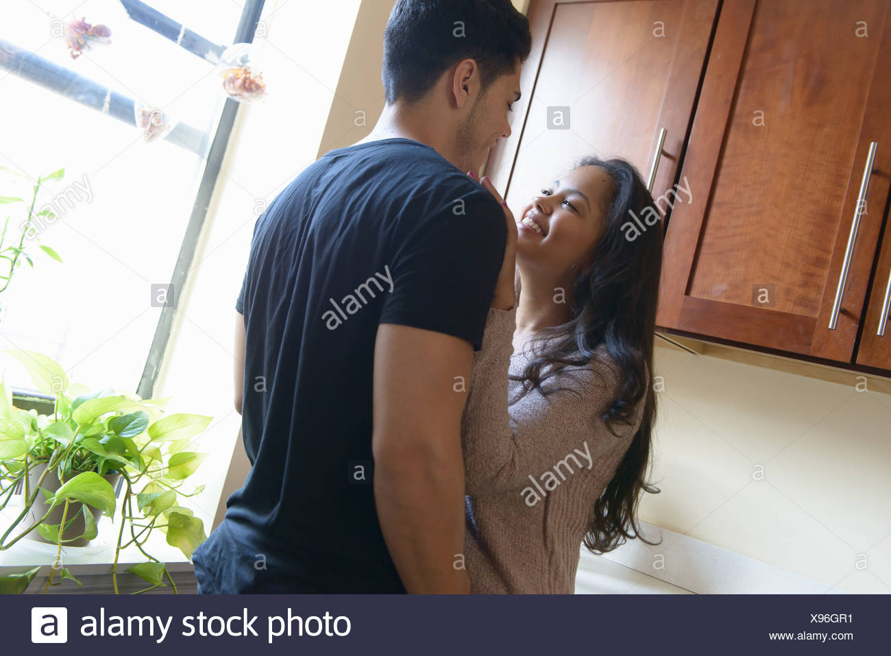 Jeune couple standing in kitchen Photo Stock