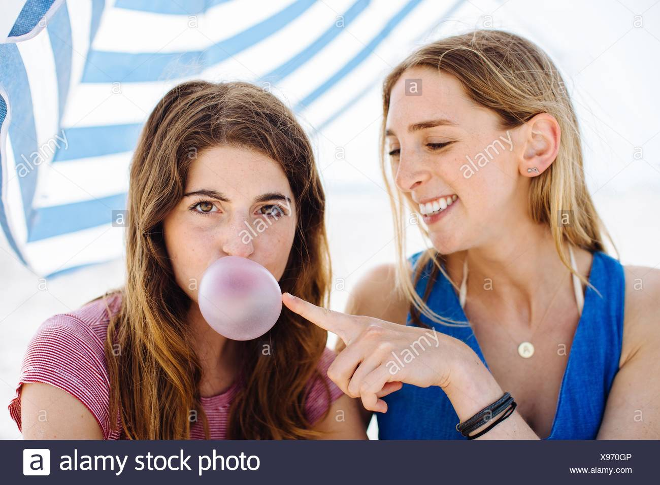 Portrait de deux jeunes amies popping bubble-gum on beach Photo Stock