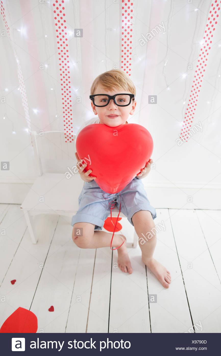 Jeune garçon posant pour une photo dans un studio de photographes, holding red balloons. Photo Stock