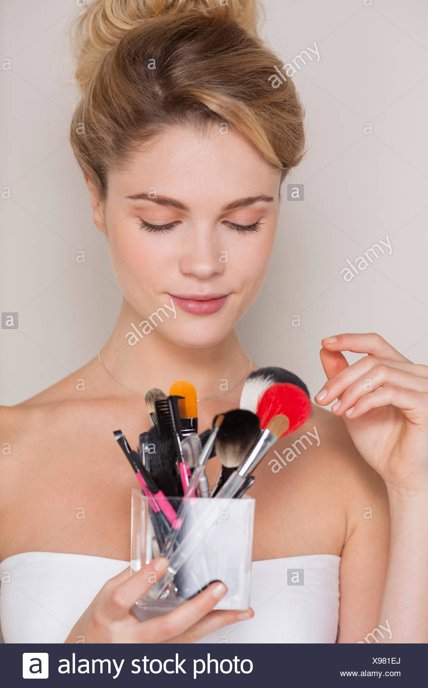 Belle femme tenant un assortiment de Pinceaux de maquillage Photo Stock