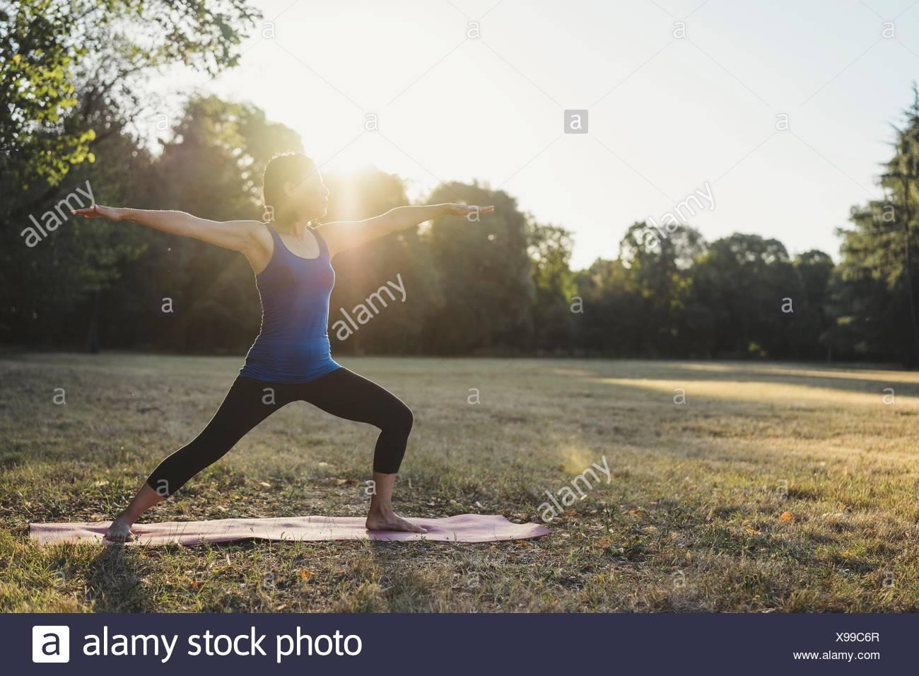 Mature Woman in park, debout en position de yoga, les bras tendus Photo Stock