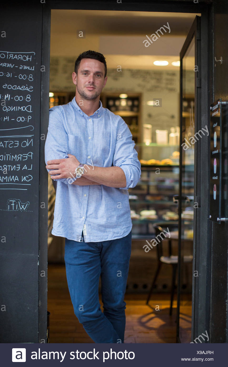 Portrait of mid adult male cafe owner leaning against cafe porte Photo Stock