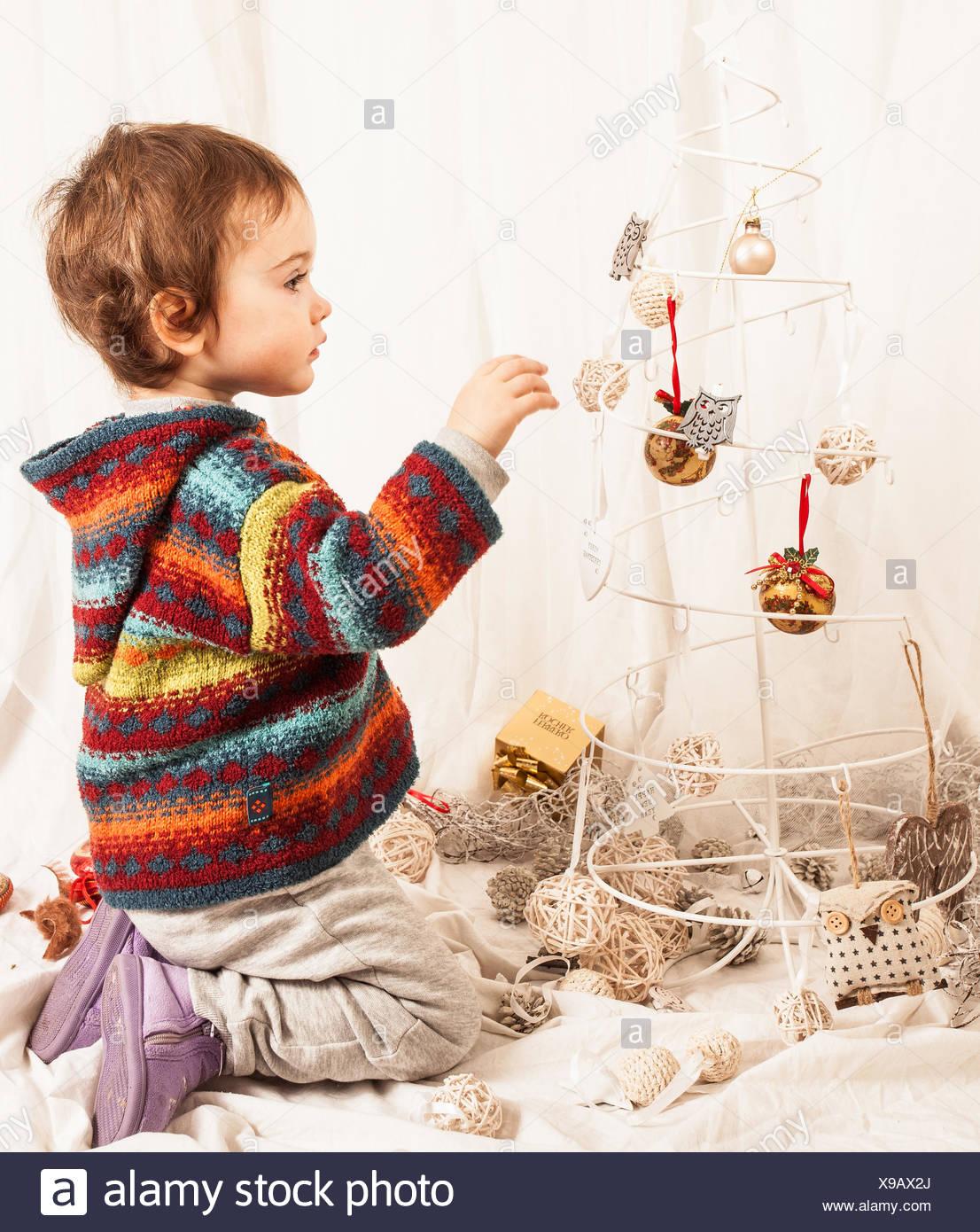 Garçon jouant avec décoration de Noël sur le lit chez lui Photo Stock