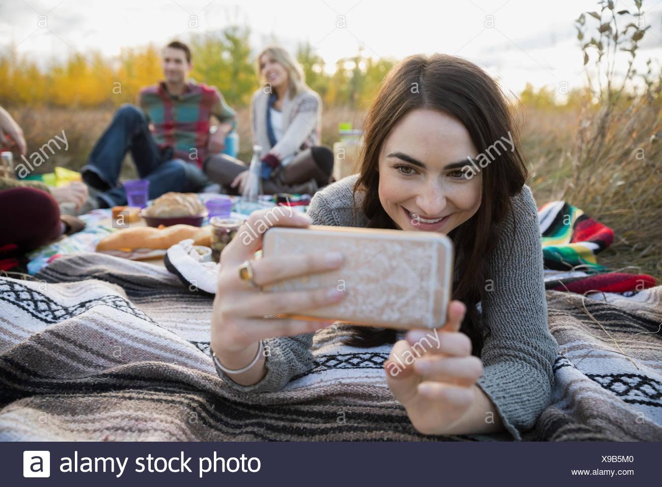 Jeune femme prenant sur selfies couverture de pique-nique dans le champ Photo Stock