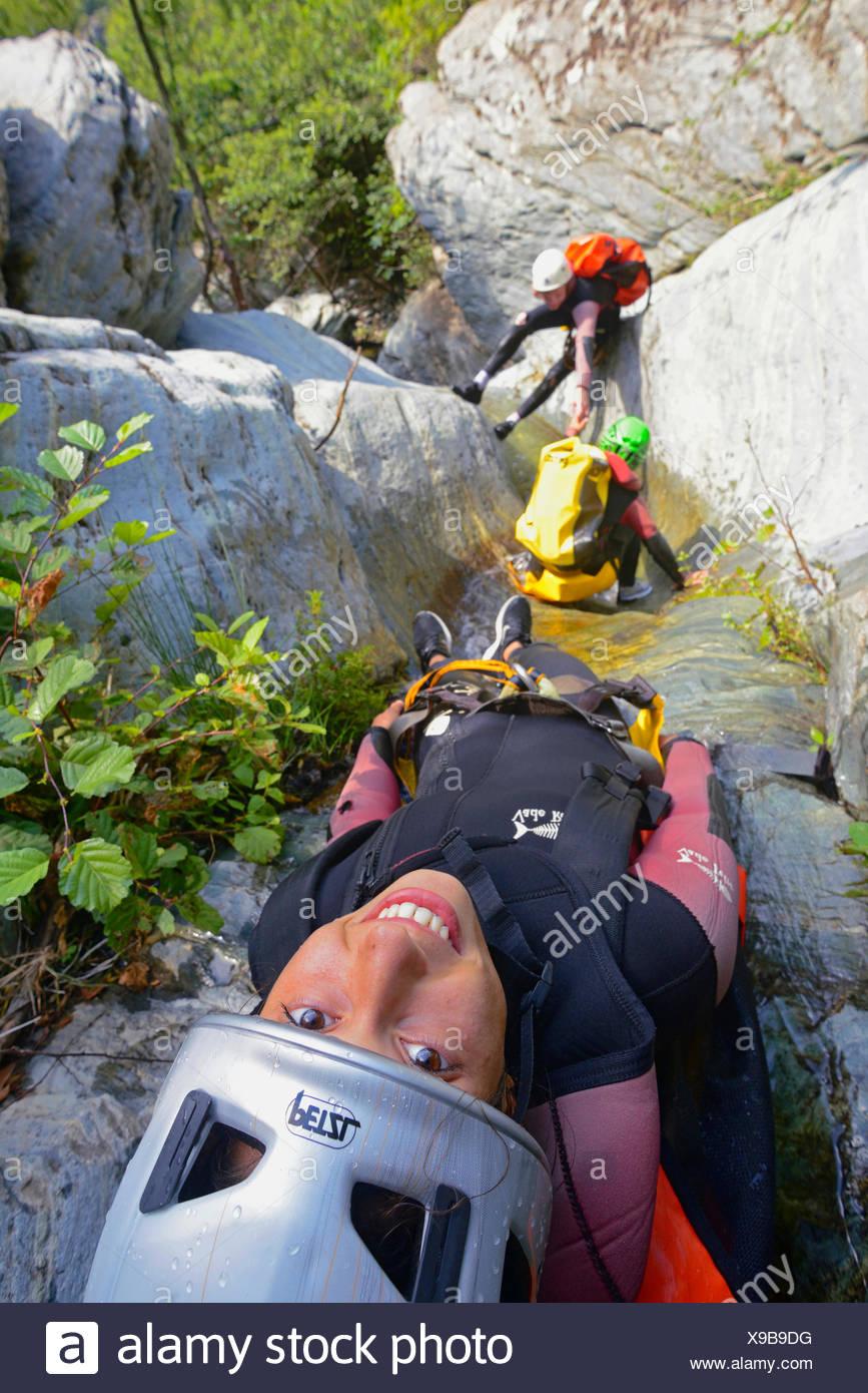 Trois personnes à glisser à travers un rocky creek, canyoning, France, Corse, Bastia, Canyon de Cipettu Photo Stock
