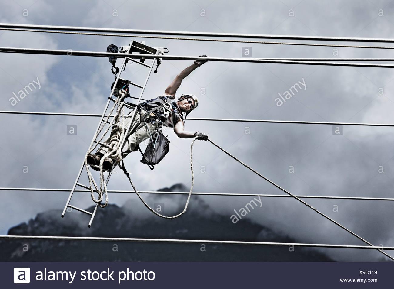 Technicien de service haute tension tirant une corde pour obtenir au prochain pylône Banque D'Images