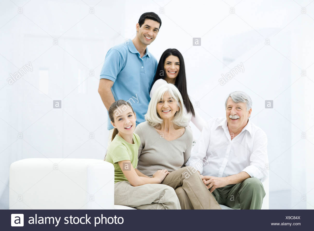 Multi-generation family smiling at camera, portrait Photo Stock