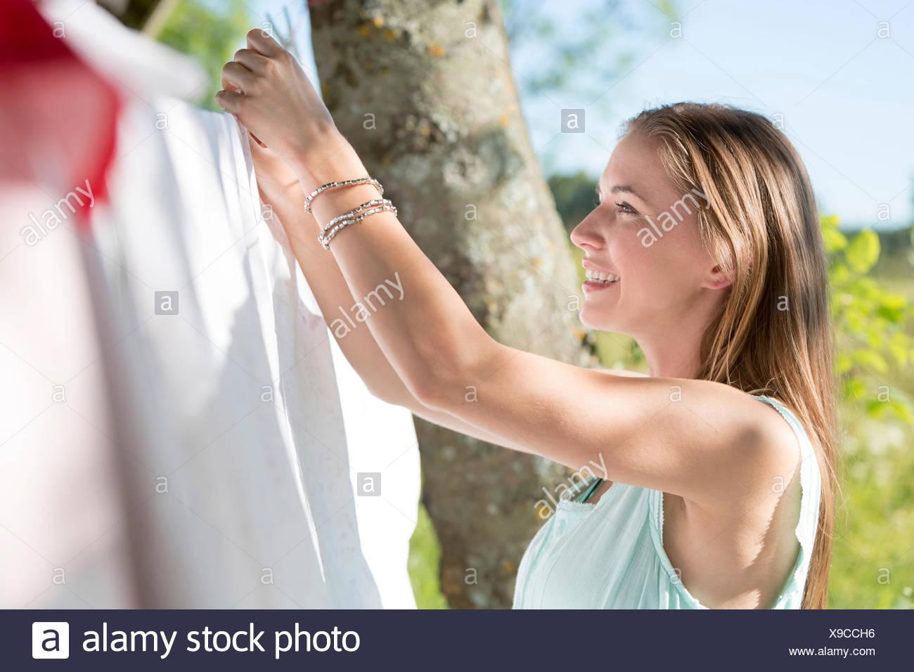Souriante jeune femme étendre le linge sur la corde à linge Photo Stock