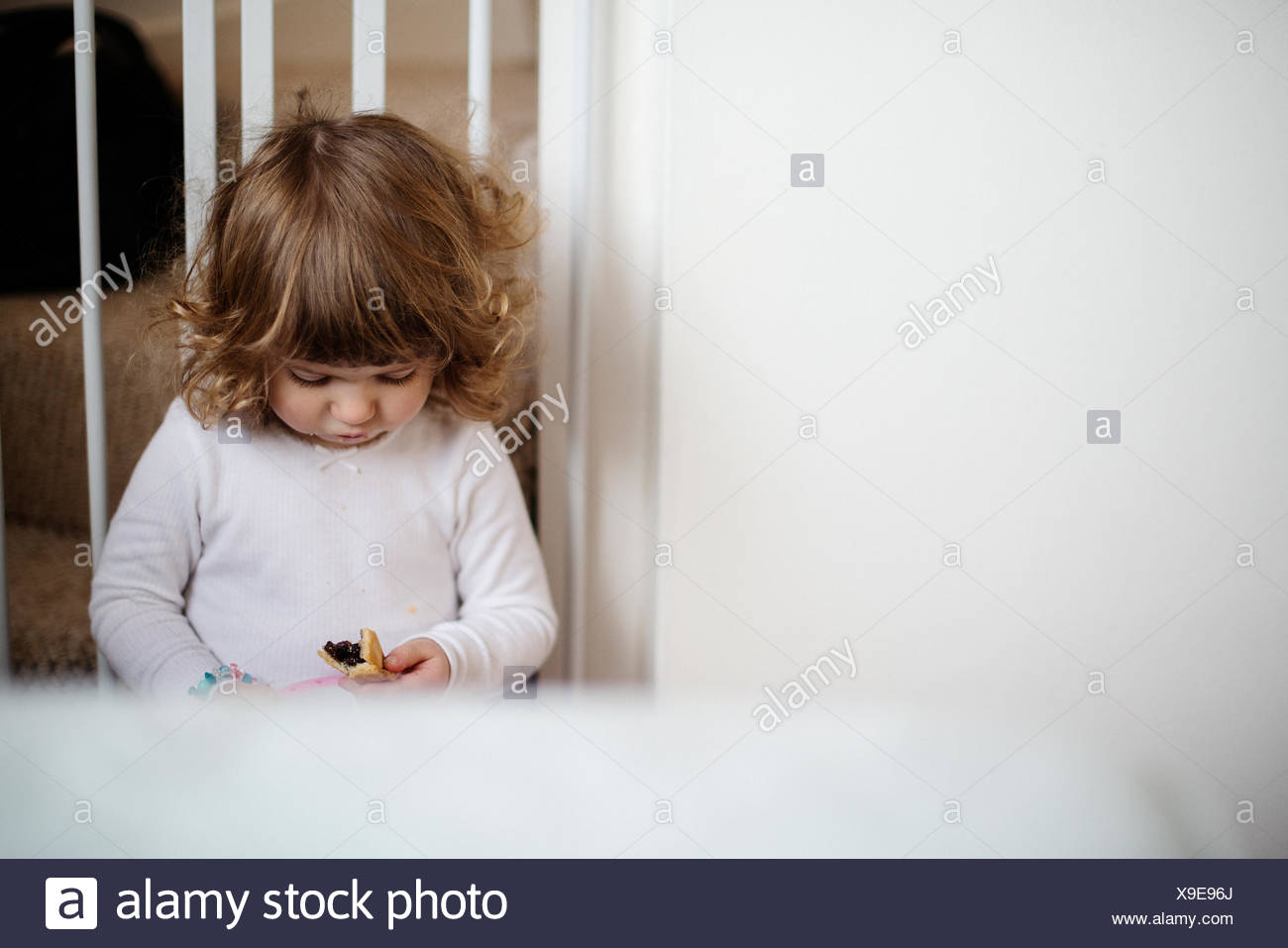 Girl eating snack sur escaliers Photo Stock