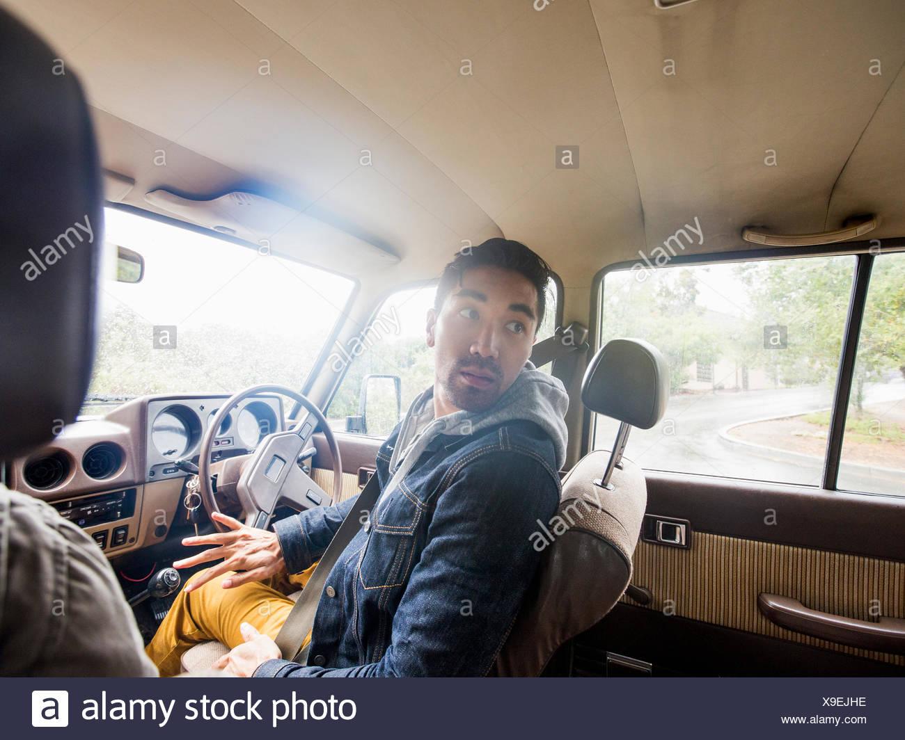 Jeune homme dans une voiture, sur le siège du conducteur, regardant par-dessus son épaule Photo Stock