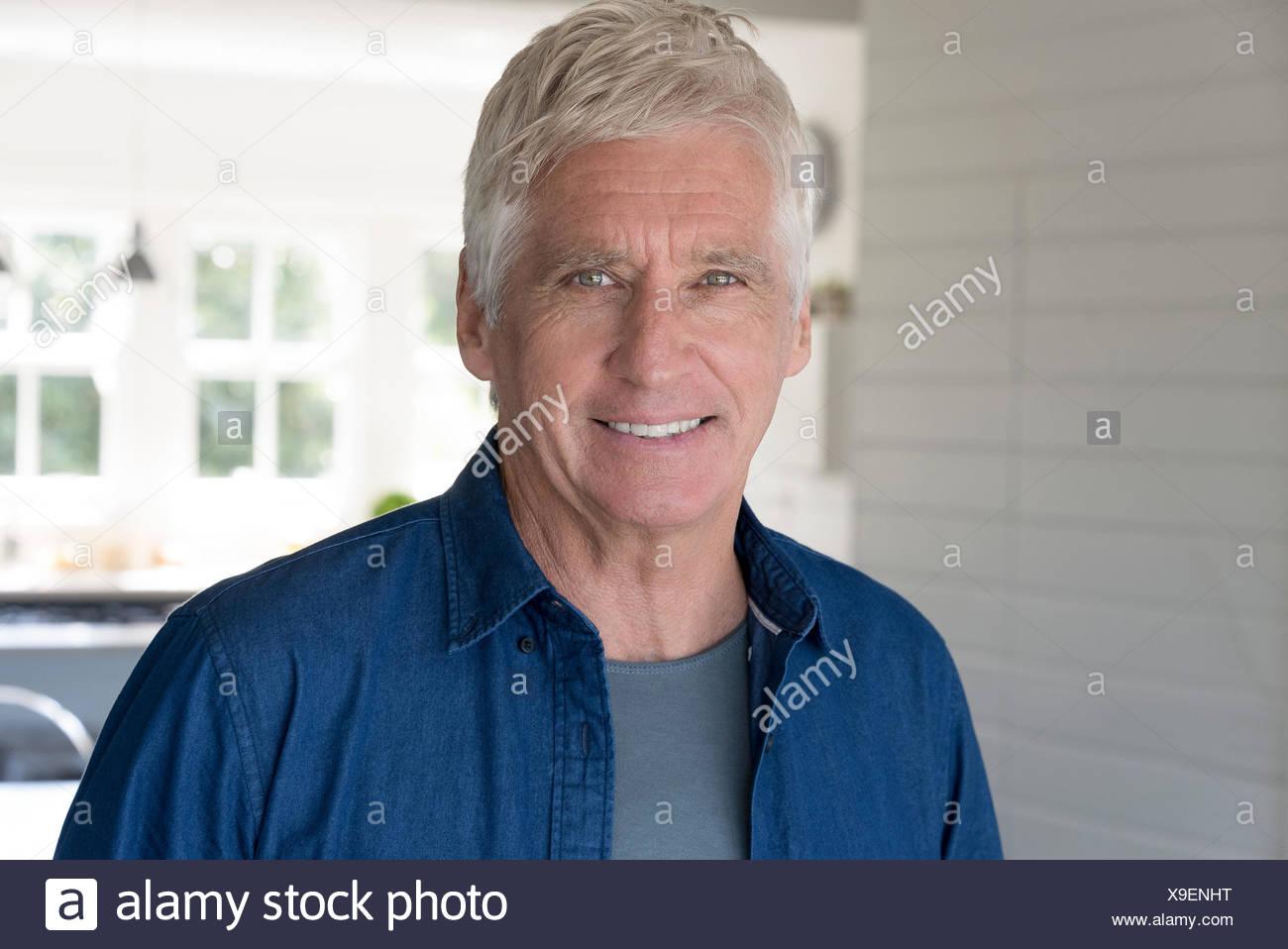 Portrait of happy senior man smiling at home Photo Stock