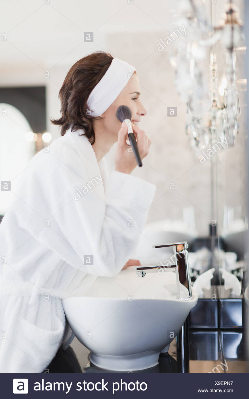 Peignoir femme en appliquant le maquillage Banque D'Images