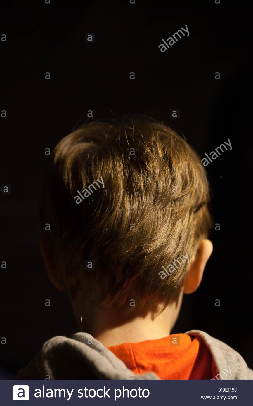 Vue arrière du garçon avec les cheveux bruns sur fond noir Photo Stock