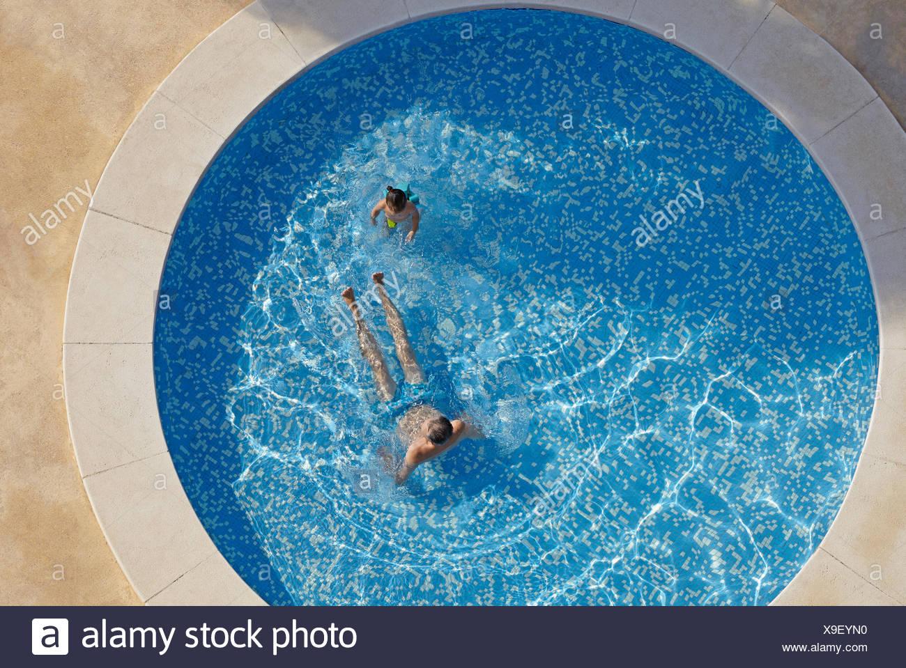Vue aérienne de l'homme et d'enfant en fille en piscine Photo Stock