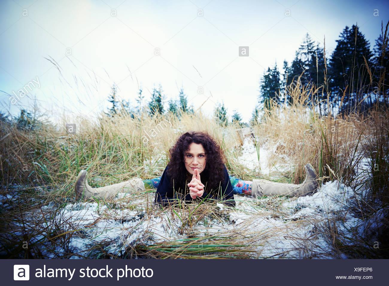 Mid adult woman pratiquant les scissions dans l'aménagement forestier Photo Stock