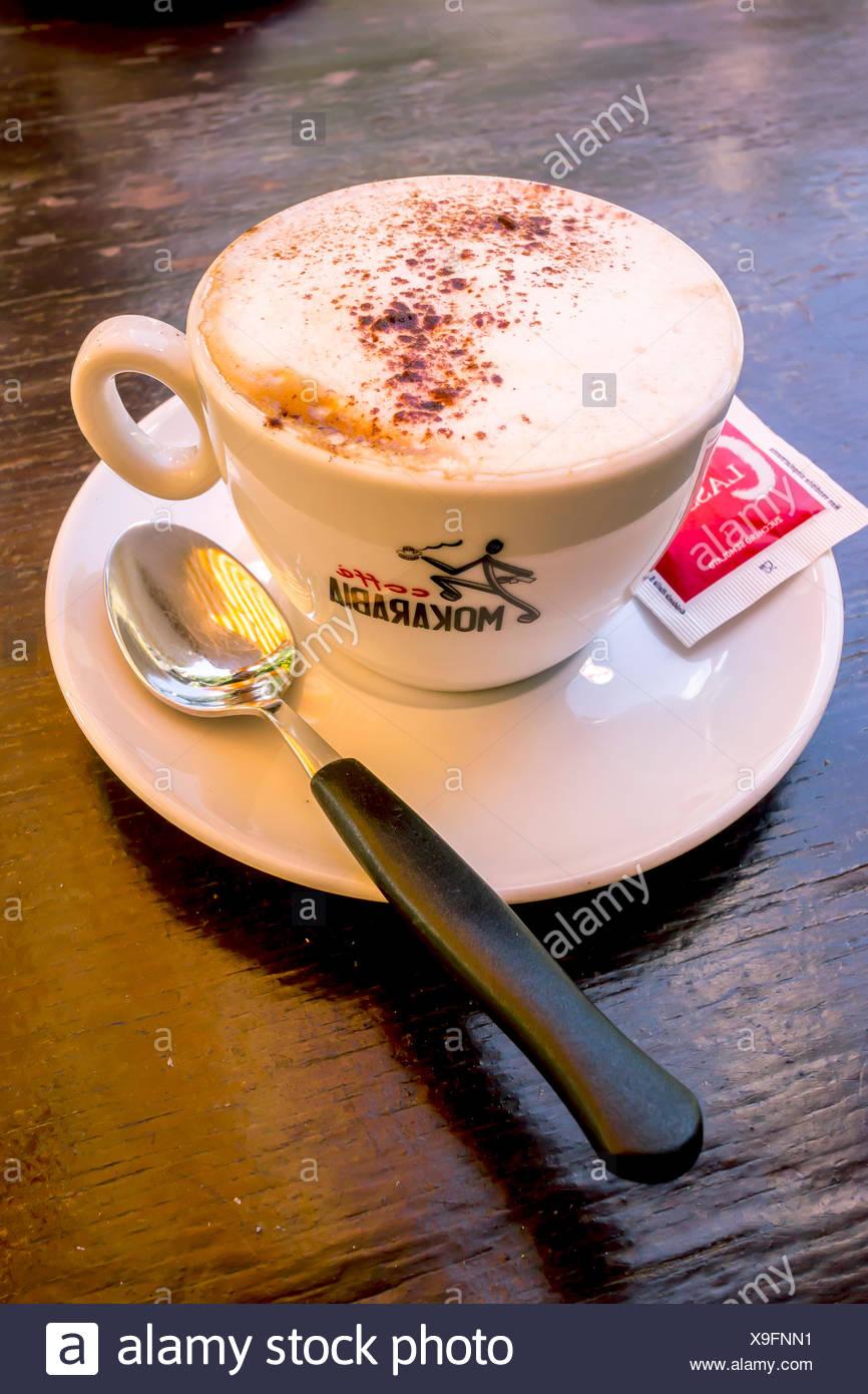 Cappuccino avec un sachet de sucre et une cuillère, Italie Photo Stock