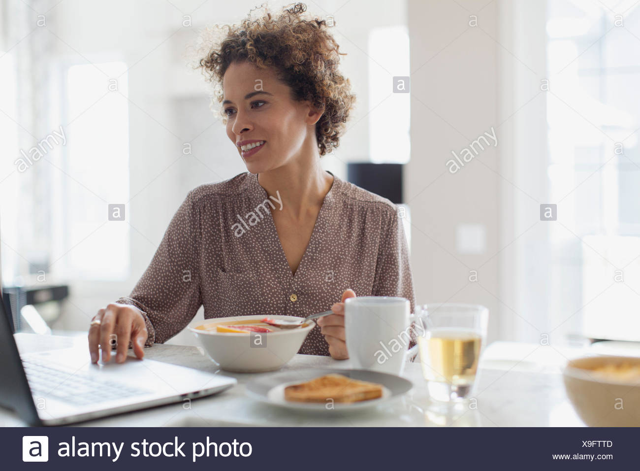 Woman using laptop pendant son petit déjeuner. Photo Stock