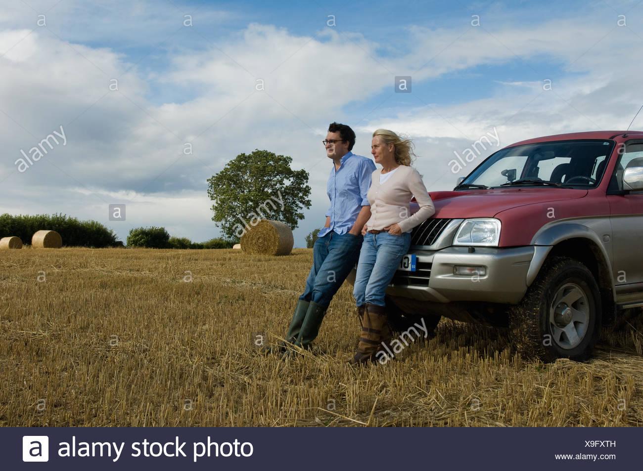 Appuyé contre la mère et le fils d'entraînement à quatre roues dans le champ moissonné Photo Stock