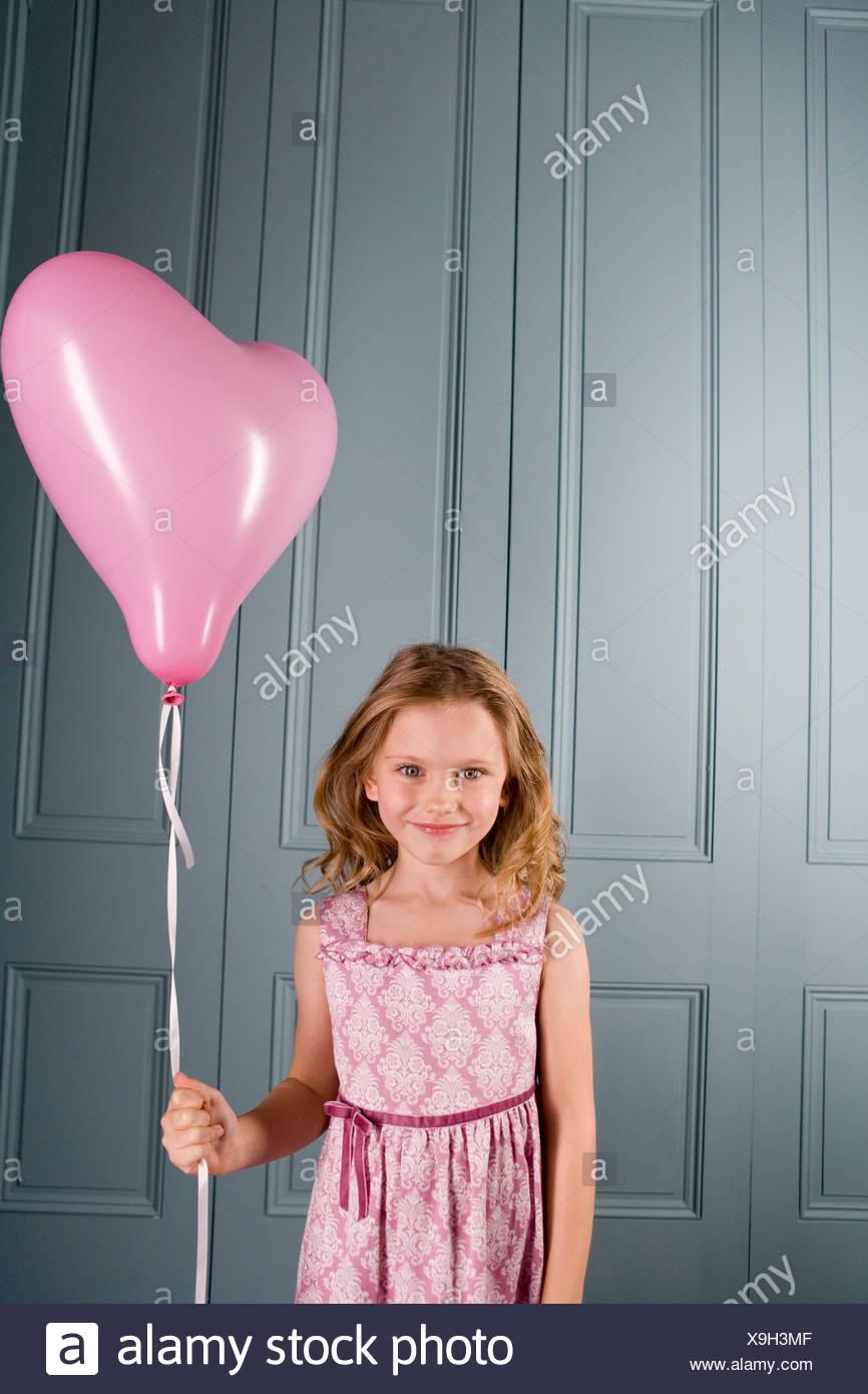 Petite fille en robe de soirée rose holding heart shaped balloon Banque D'Images