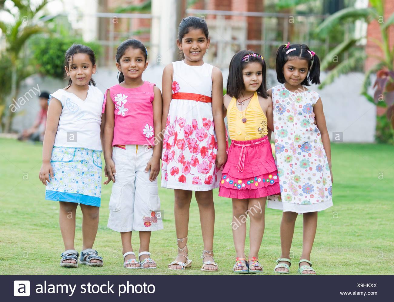 Cinq filles debout dans une pelouse et souriant Photo Stock