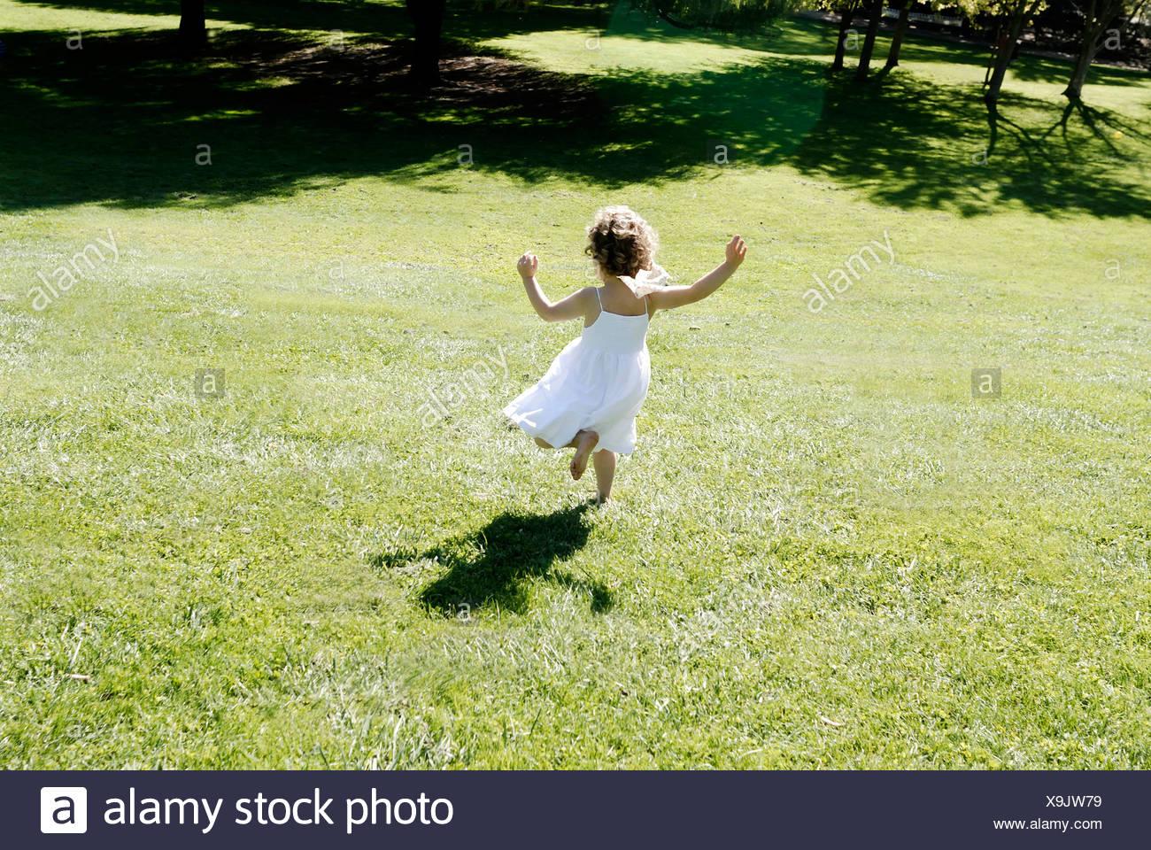 3 ans fille courir dans un champ Photo Stock