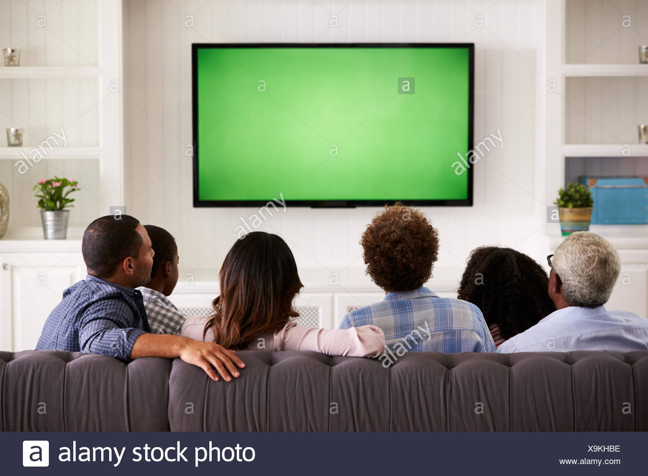 Multi Generation Family Watching Tv A La Maison Vue De Dos Banque D