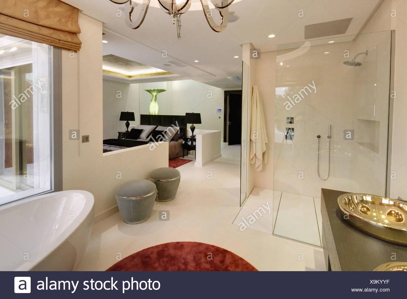 Grande douche à l\'\'italienne et des tabourets gris dans une salle de ...
