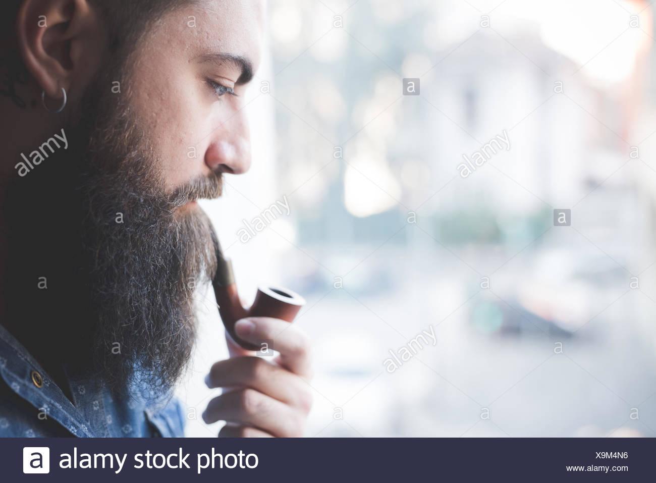 Jeune homme barbu pipe par fenêtre Photo Stock