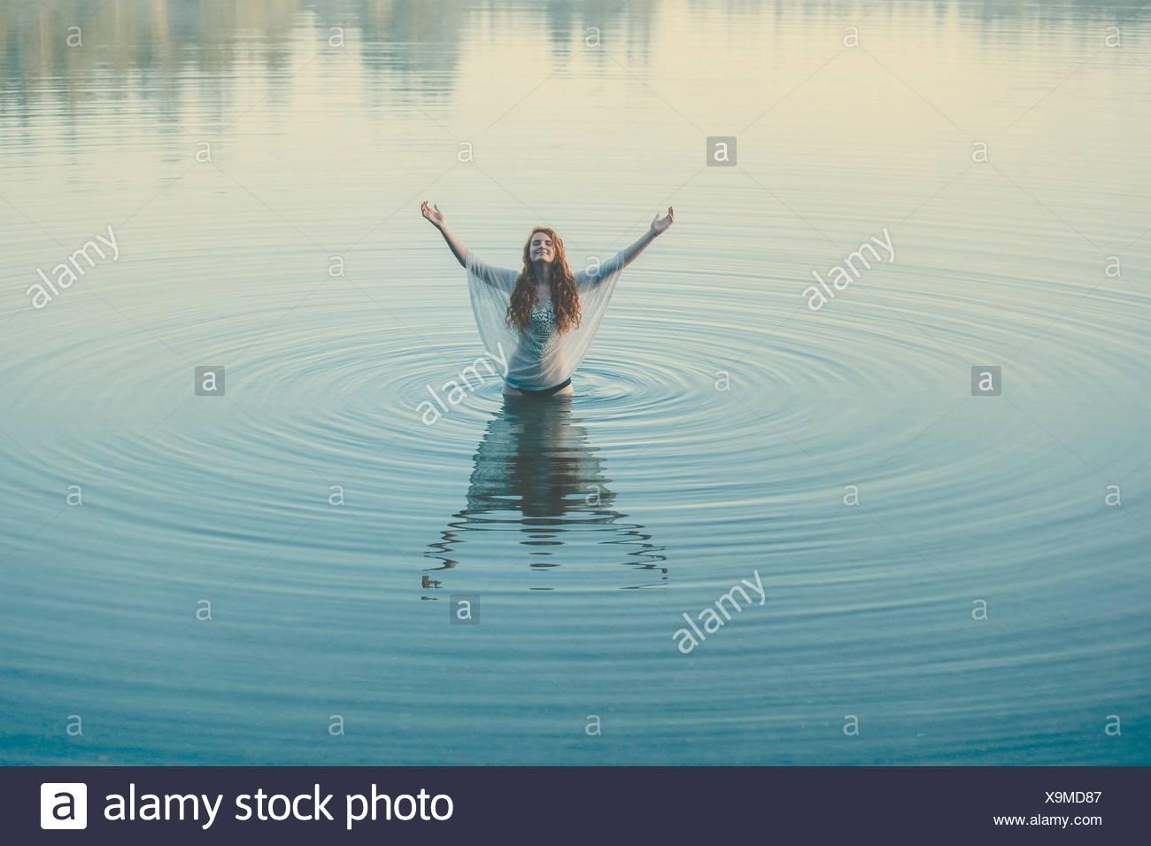 Jeune femme debout au milieu du lac ondulations avec bras ouverts Photo Stock