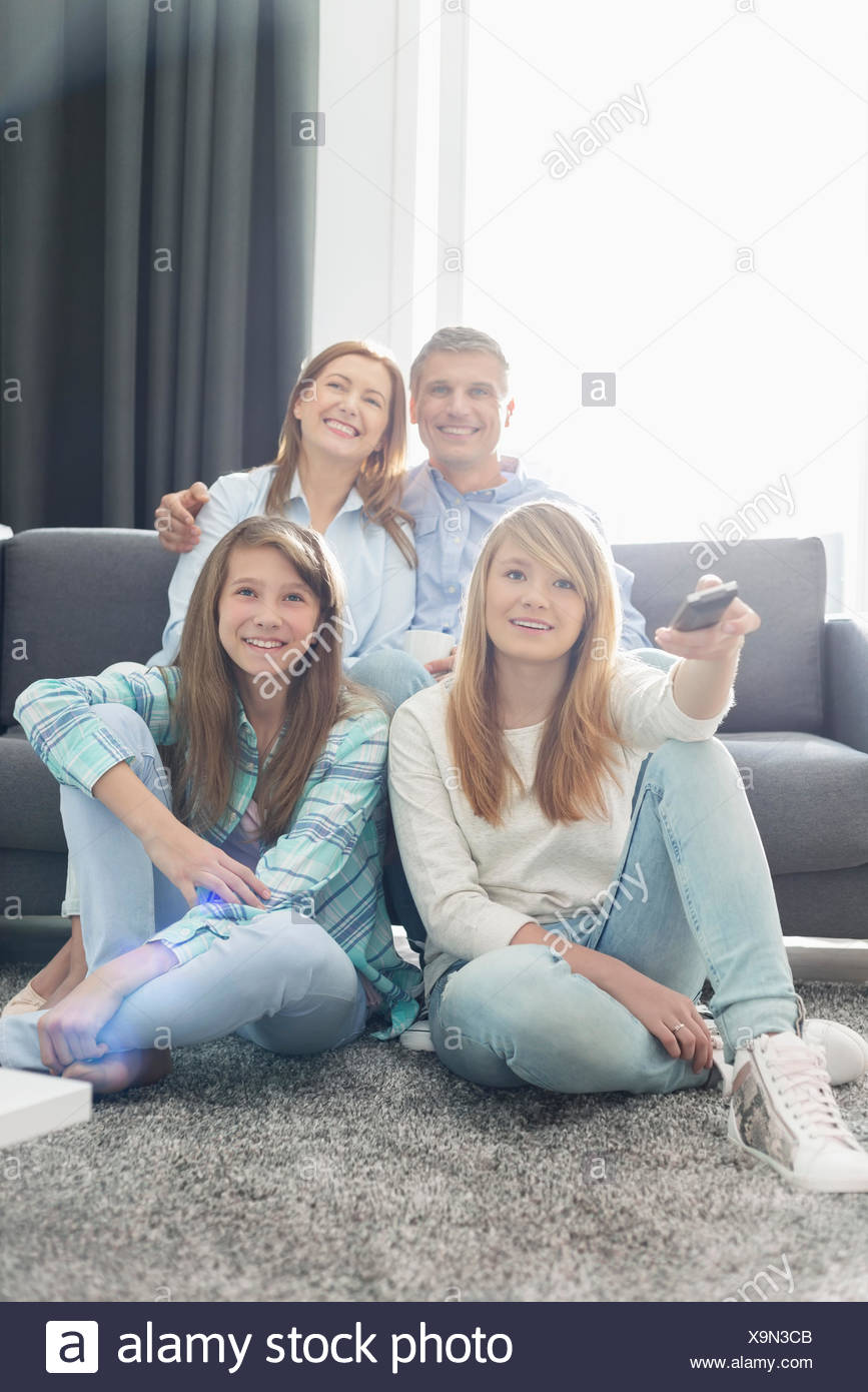 Famille de quatre heureux ensemble à la maison à regarder la télévision Photo Stock