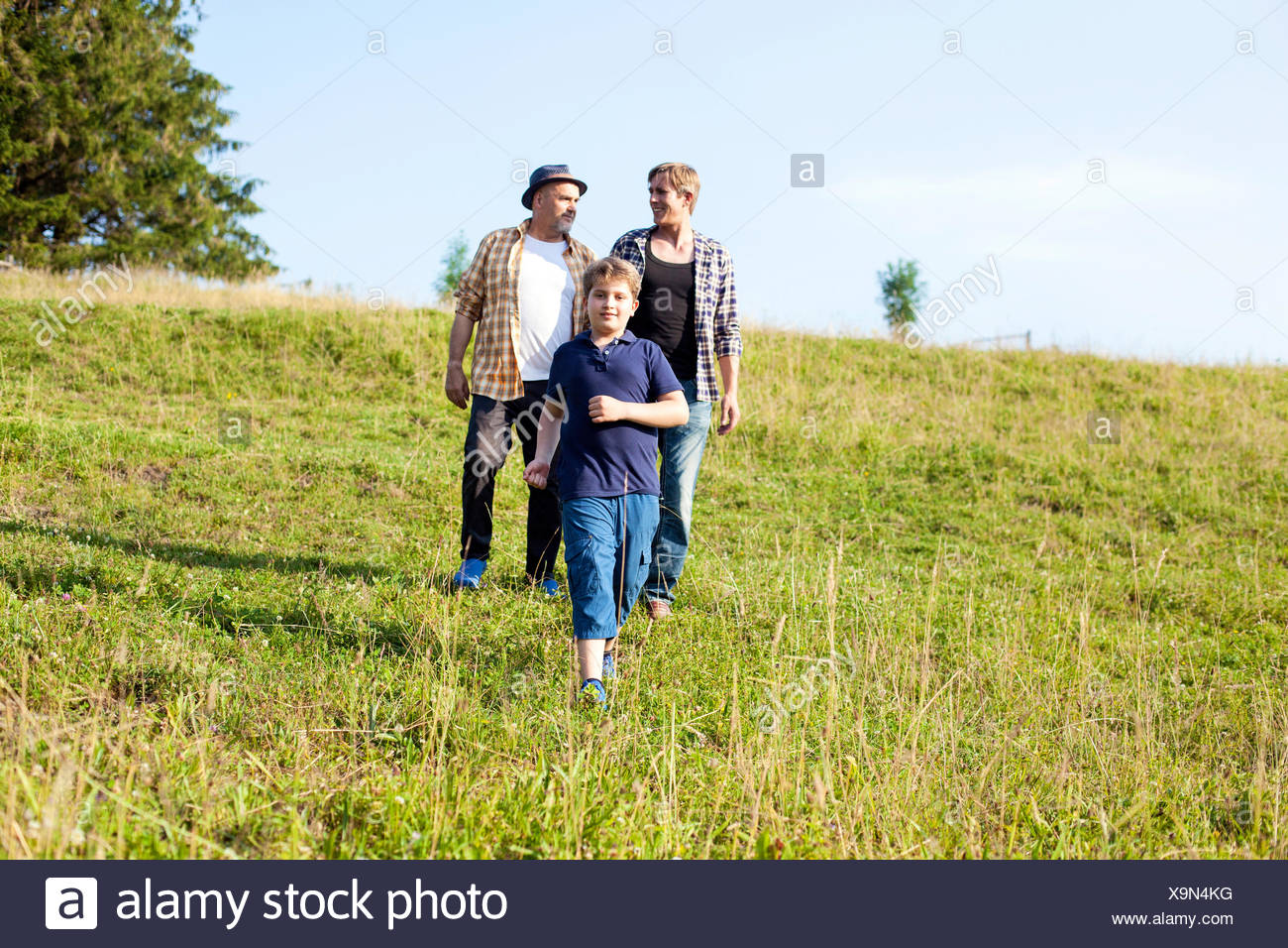 Multi-generation family walking in the meadow Photo Stock
