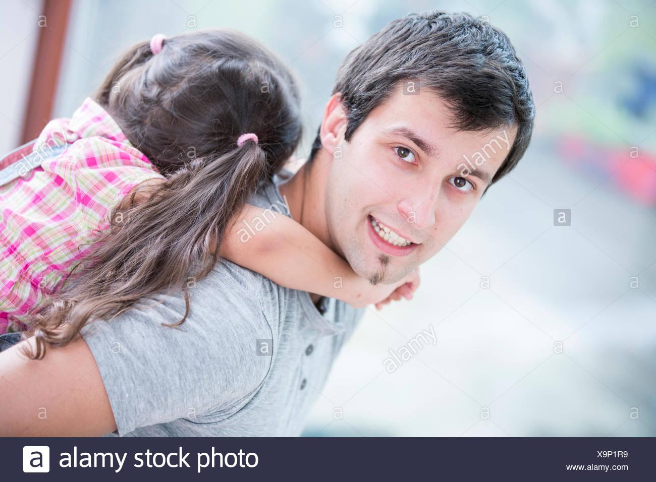 Side view portrait of young man piggybacking petite fille à la maison Banque D'Images