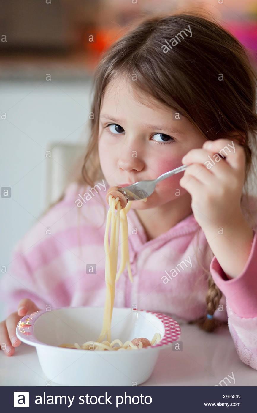 Little girl (4-5) mange du spaghetti pour le déjeuner Photo Stock