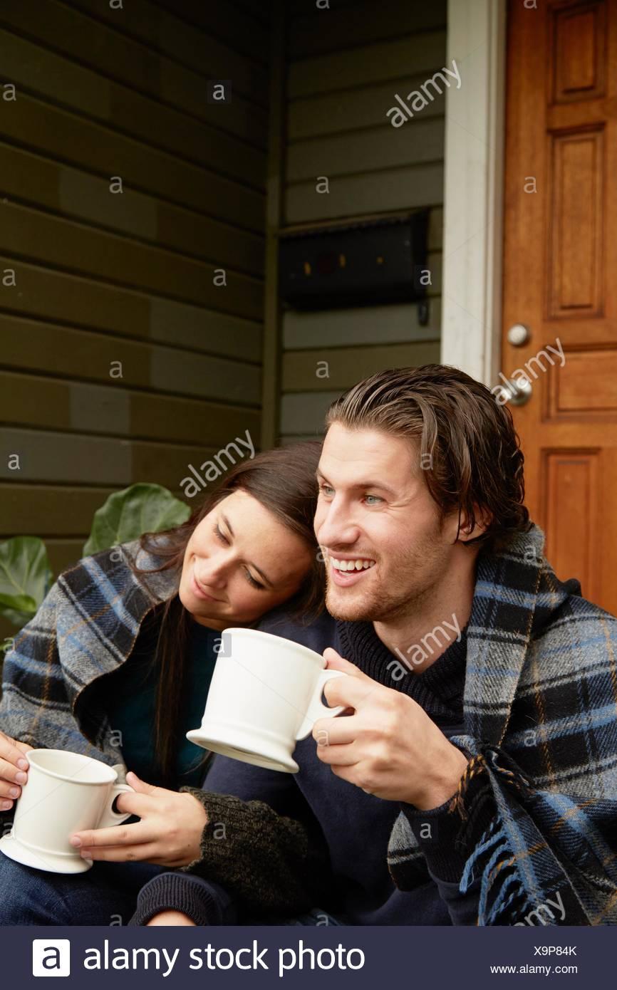 Young couple sitting on porch étape enveloppés de blanket Photo Stock