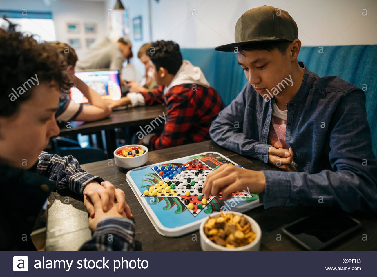 Le Tween boy amis jouant au Chinese checkers cafe table Photo Stock