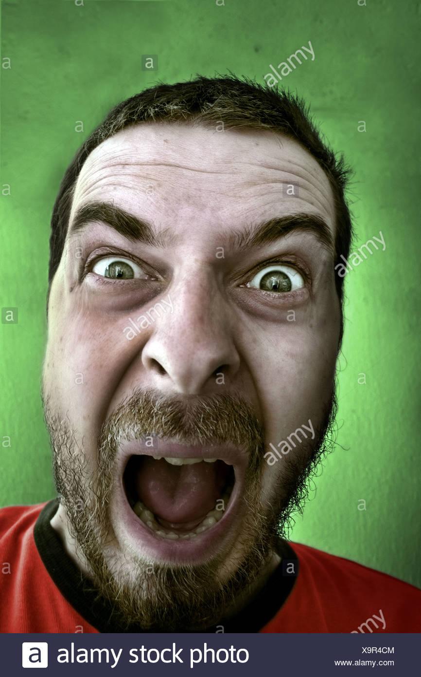 Portrait de l'homme criant choquée avec de grands yeux craintifs et Photo Stock