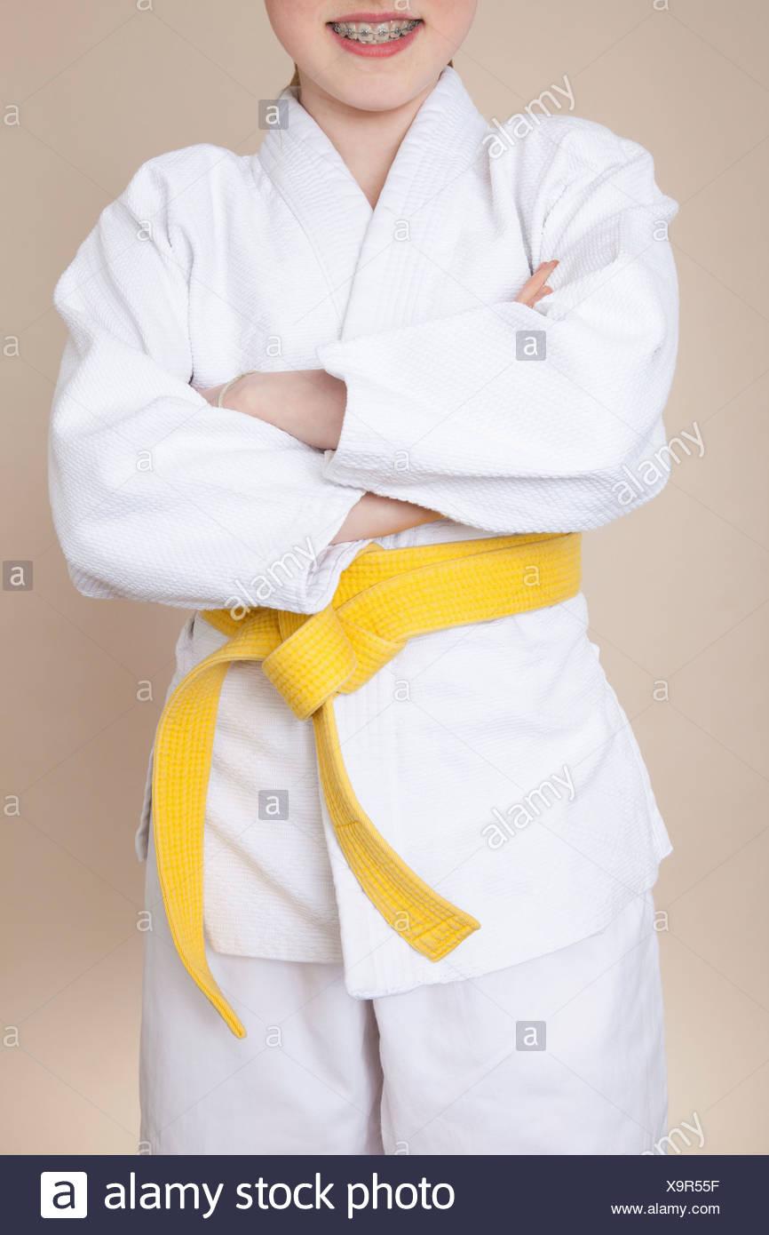 6395ca785f502 A smiling girl with arms crossed portant uniforme d arts martiaux avec  ceinture jaune