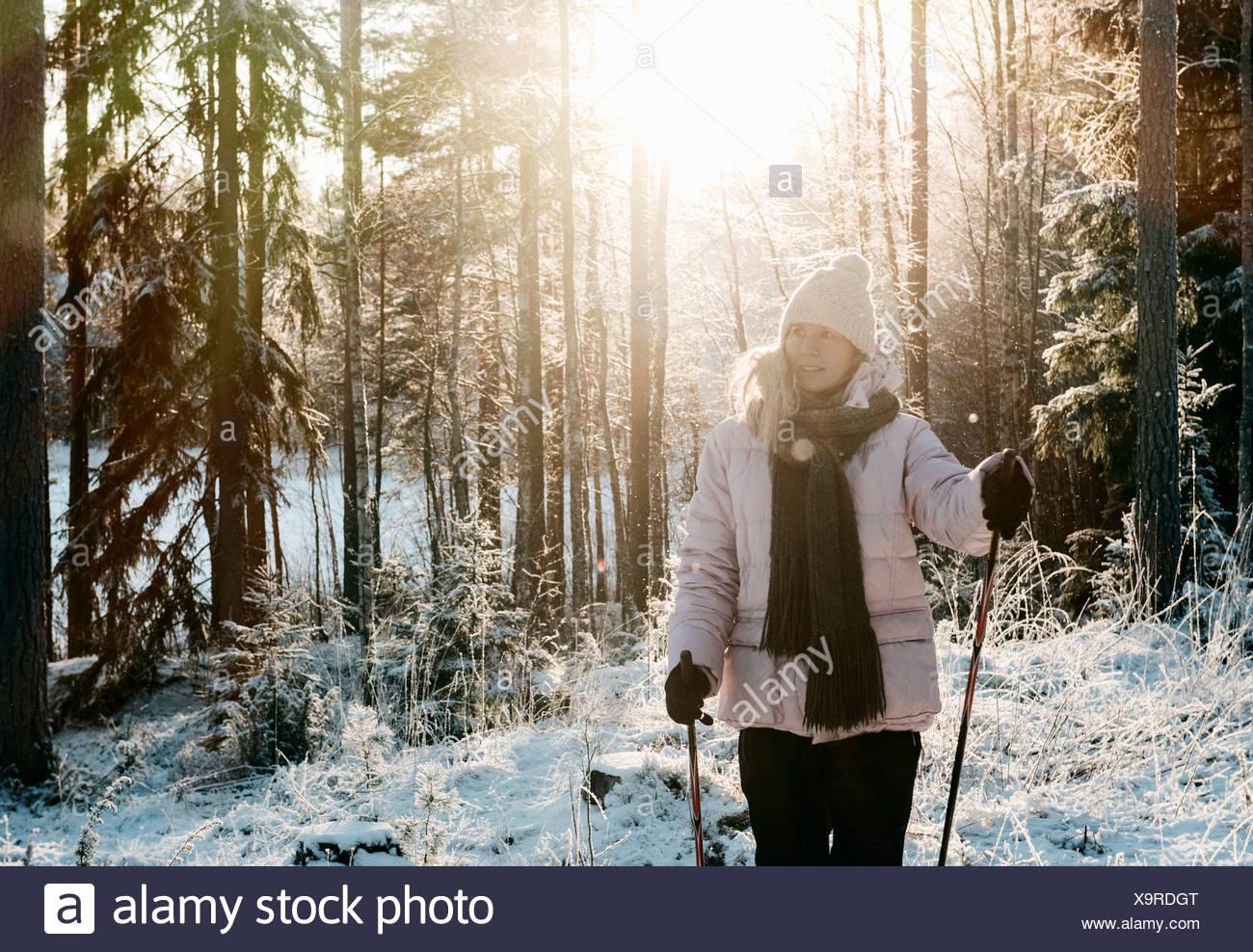 Mid adult woman marche nordique dans la forêt couverte de neige Photo Stock