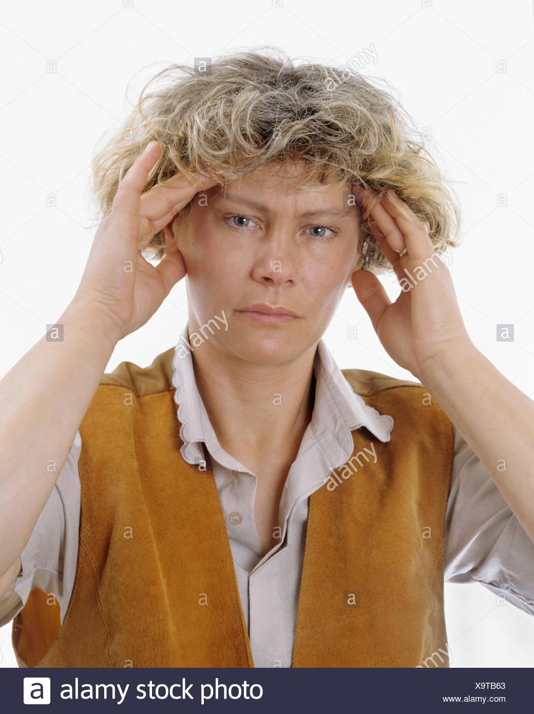 Une femme blonde tient la tête à deux mains, maux de tête intenses, migraine, surcharge Photo Stock