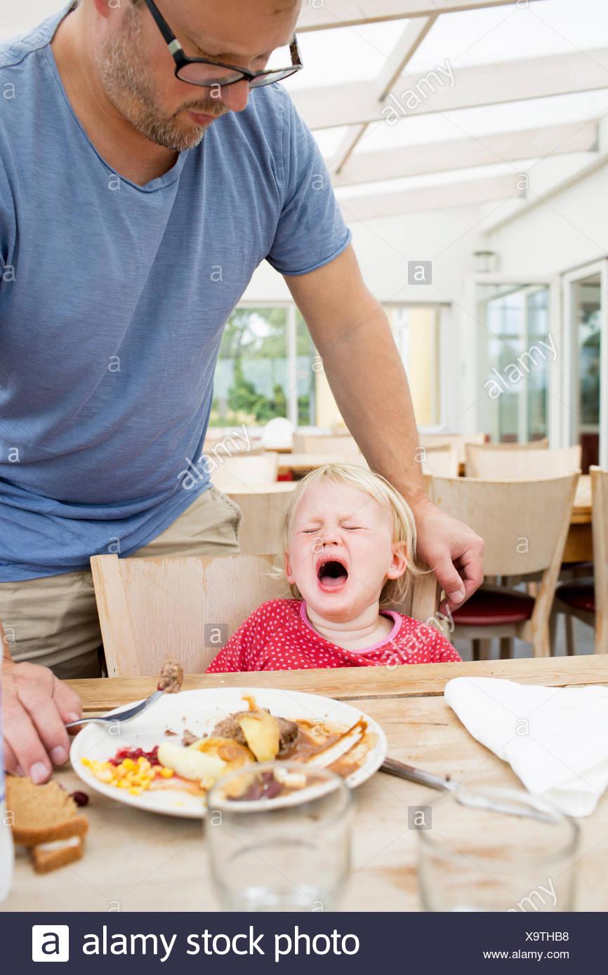 Une jeune fille pleurer à la table de dîner Photo Stock