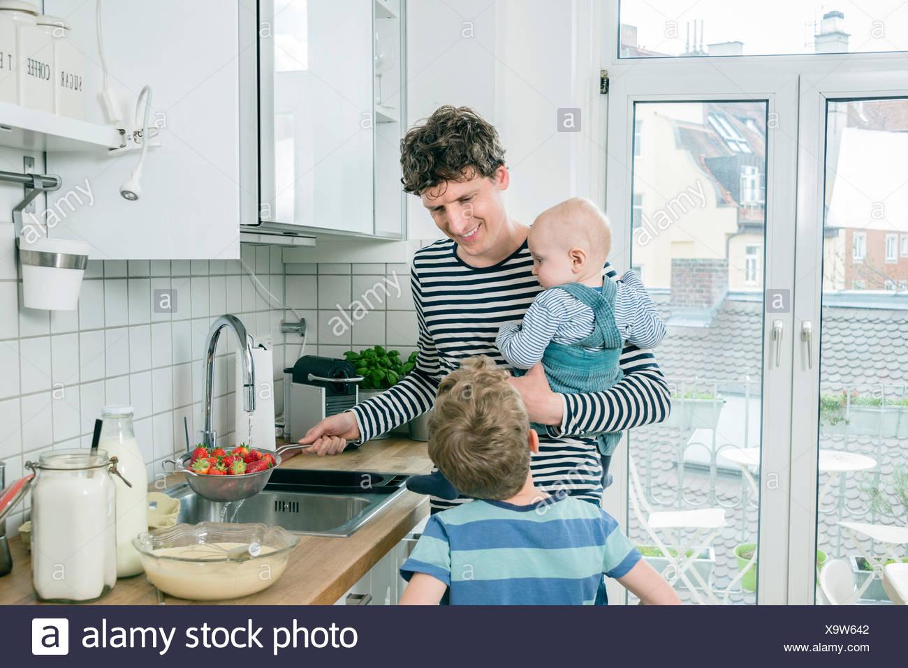 Père prépare la nourriture tout en tenant bébé dans Cuisine Photo Stock