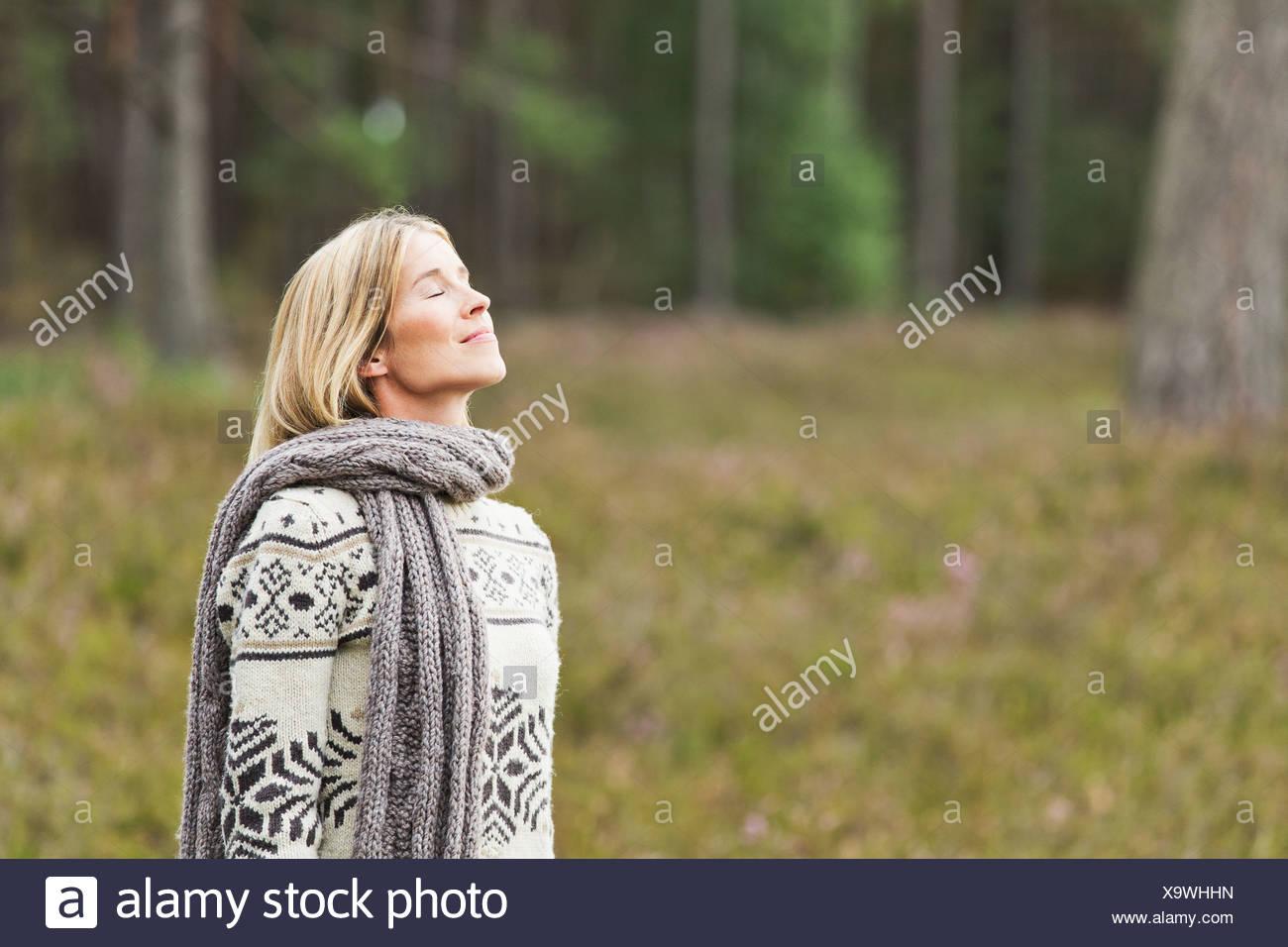 Mid adult woman wearing sweater avec les yeux fermé Photo Stock
