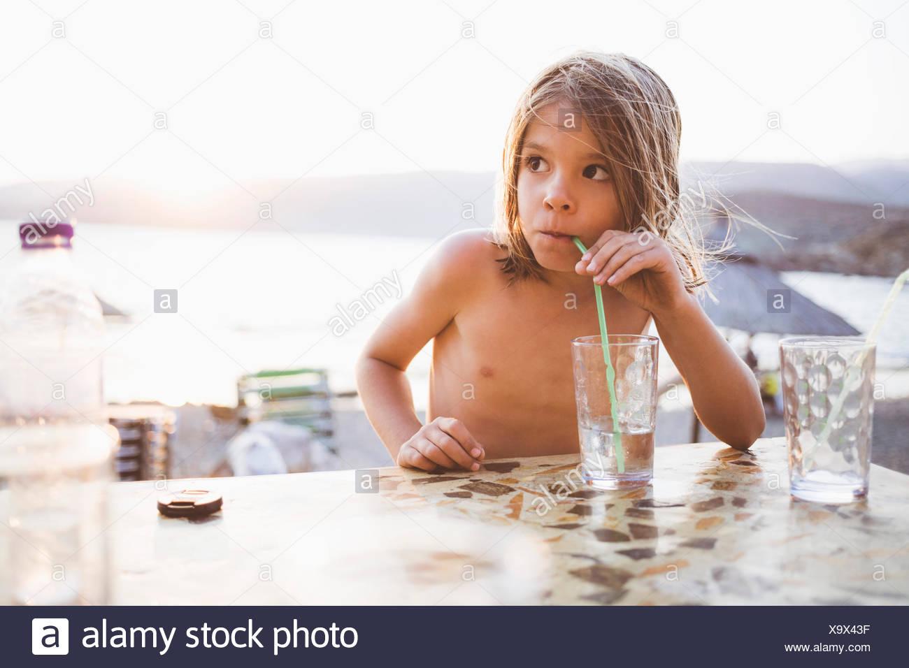 Garçon ayant un verre dans lakeside Photo Stock