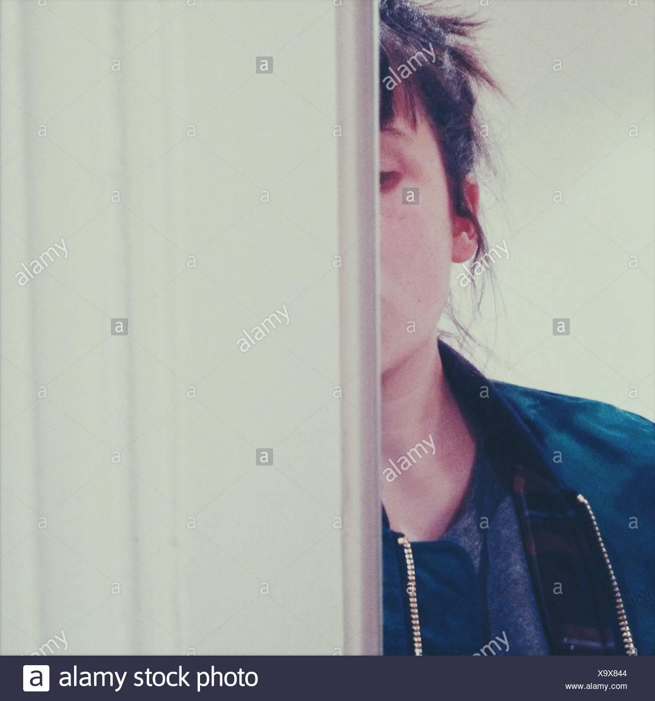 Portrait de femme se cachant derrière le mur Photo Stock