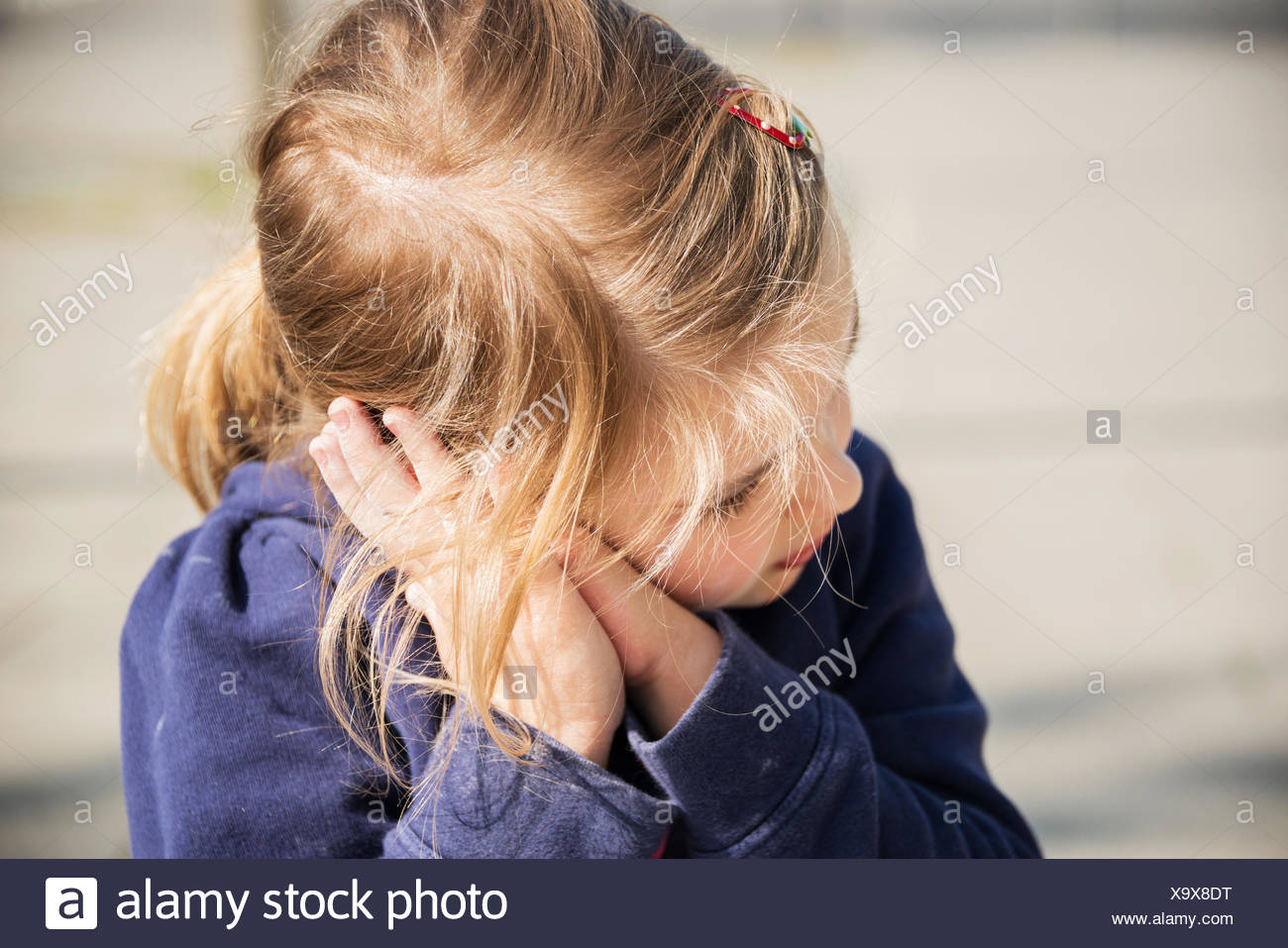Blonde girl resting head in hands, Munich, Bavière, Allemagne Photo Stock