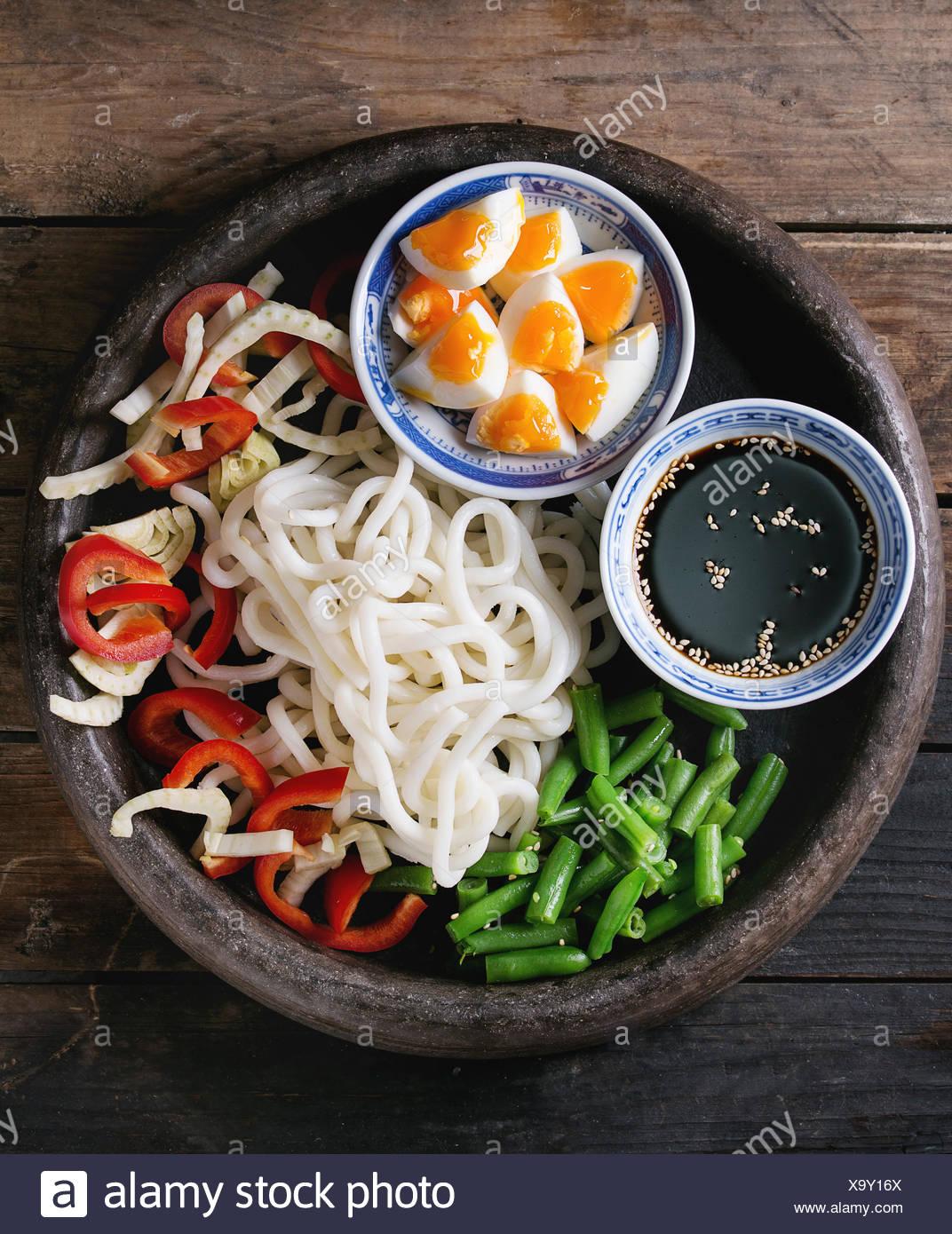 Ingrédients pour la cuisson faire revenir les nouilles Udon, haricots verts, tranchés paprika, œufs durs, de la sauce de soja avec les graines de sésame dans des bols traditionnels dans terracott Banque D'Images