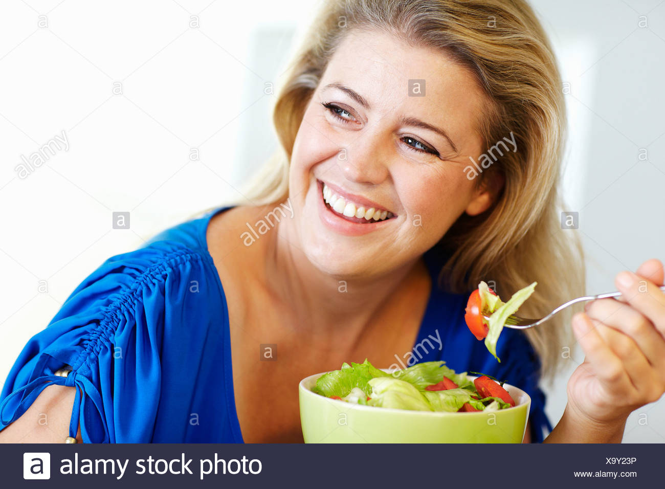 Smiling woman eating salad at table Photo Stock