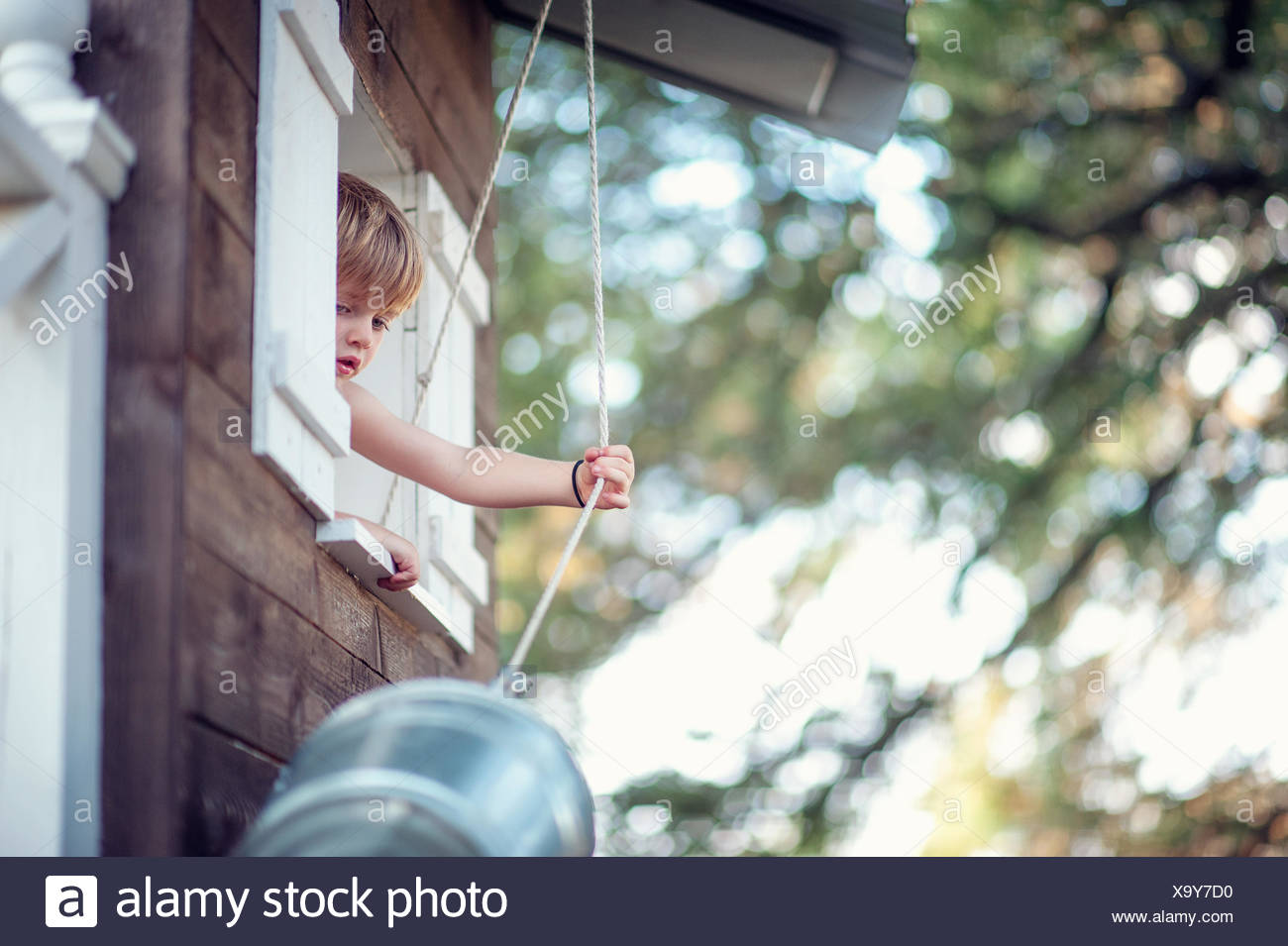 Garçon tirant un seau jusqu'à sa cabane Photo Stock