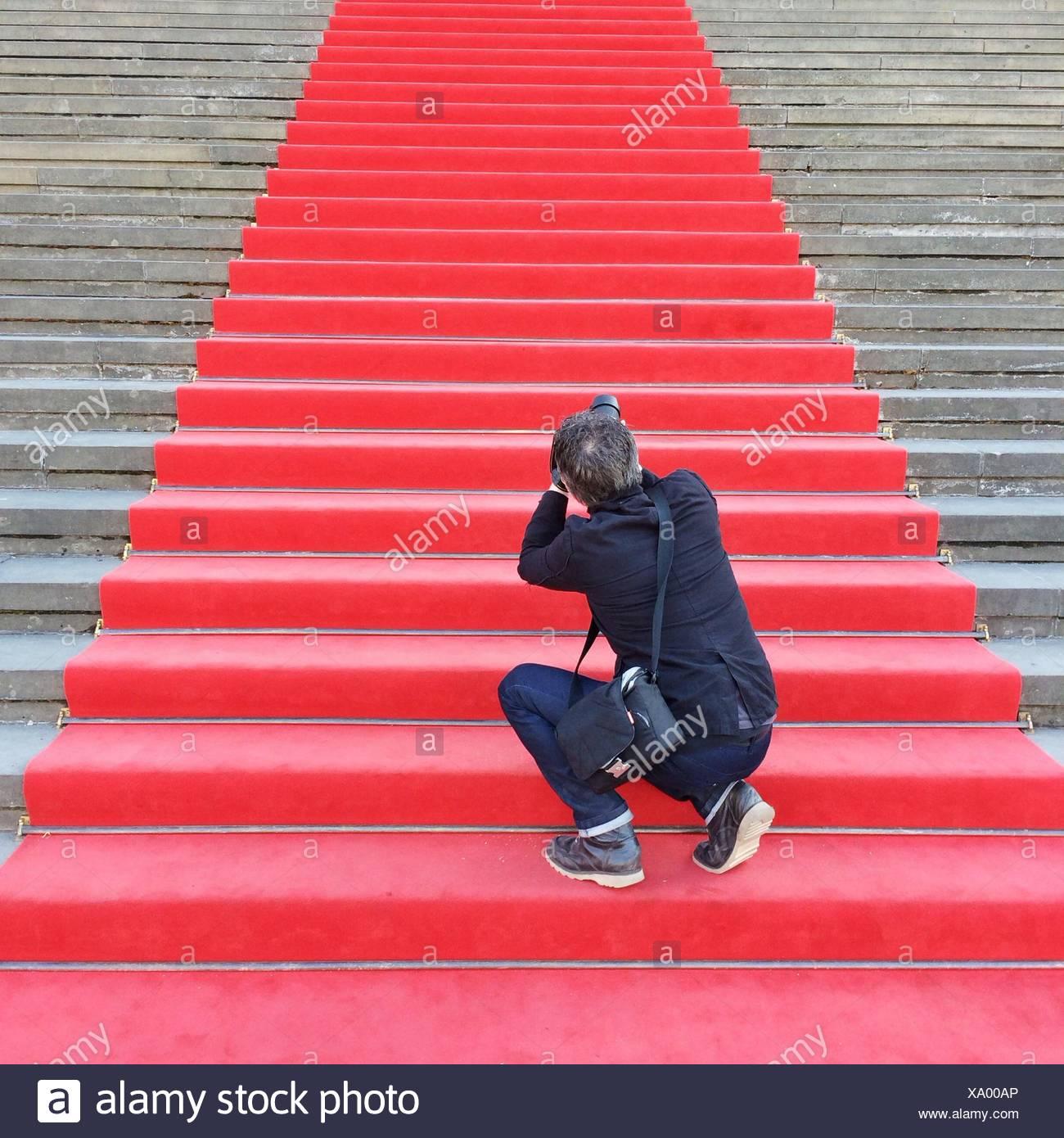Vue arrière d'un paparazzi mâle sur une moquette rouge Escaliers Photo Stock