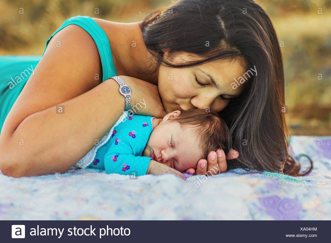 Mère embrassant sa fille nouveau-né Photo Stock